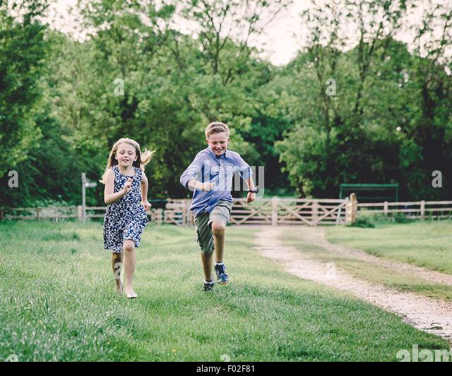 Zwei Kinder racing einander in einem Feld Stockbild
