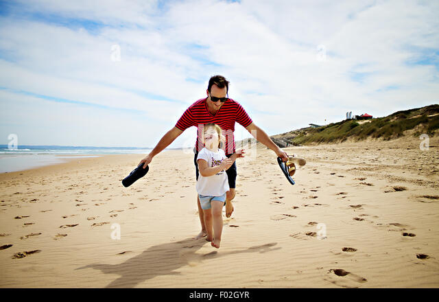 Vater und Tochter Rennen am Strand Stockbild