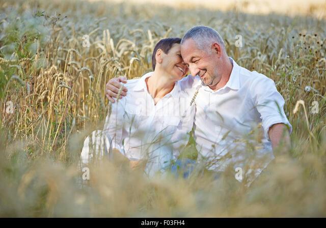 Gerne älteres Paar, sitzen in einem Weizenfeld im Sommer Stockbild