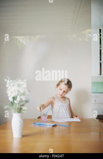 Junges Mädchen saß an einem Tisch, Malerei, eine Vase mit weißen Blüten. Stockbild