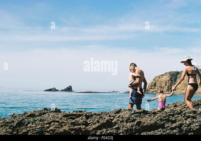 Eine Familie auf Urlaub, zwei Erwachsene mit ihrem Sohn und Tochter, die zu Fuß über Felsen am Meer. Stockbild