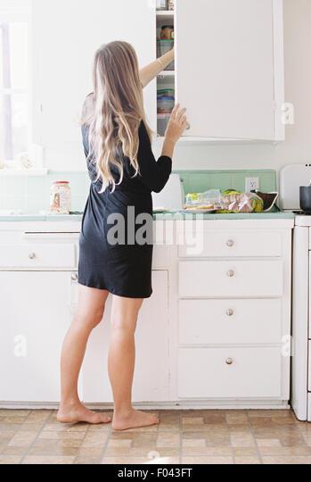 Eine Frau mit langen blonden Haaren stehen barfuß in eine Küche, einen Schrank zu öffnen. Stockbild