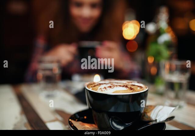 Nahaufnahme Schuss Tasse Kaffee am Tisch im Restaurant, mit einer Frau im Hintergrund. Tasse Kaffee im Fokus. Stockbild