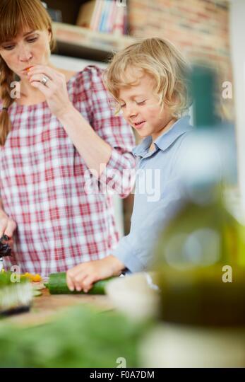 Mutter und Sohn schneiden Gurke in Küche Stockbild