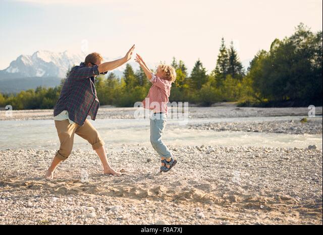 Seitenansicht des jungen Mannes und jungen springen, dabei hohe fünf, Wallgau, Bayern, Deutschland Stockbild
