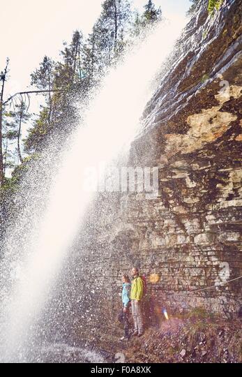 Junges Paar stehen unter Wasserfall, auf der Suche, Tirol, Österreich Stockbild