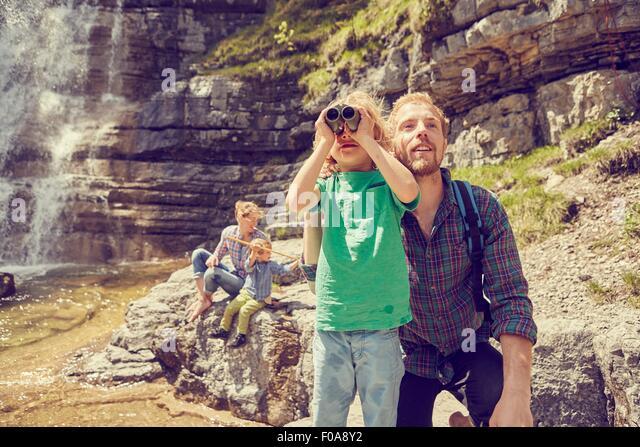 Junge Familie, die neben Wasserfall erkunden Stockbild