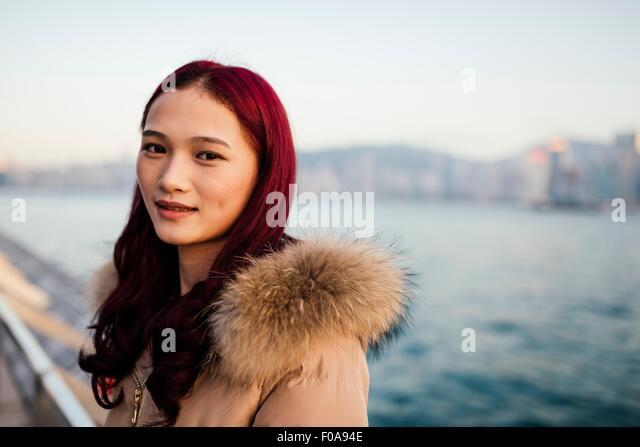Porträt der jungen Frau mit Fell Trimmen Mantel mit gefärbten roten Haaren vor Wasser Stockbild