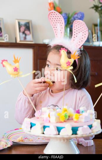 Junge Mädchen tragen Hasenohren, Kuchen essen Stockbild