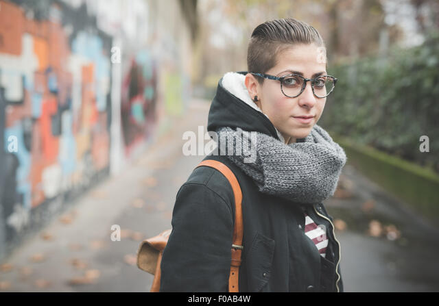 Teenager auf Straße, Graffitiwand im Hintergrund Stockbild