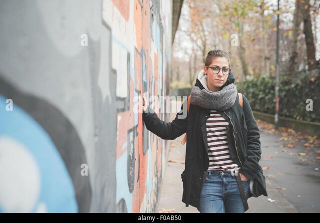 Teenager, die Graffitiwand gelehnt Stockbild