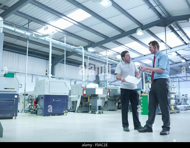 Ingenieur und Lehrling diskutieren Zeichnungen in Fabrik Stockbild
