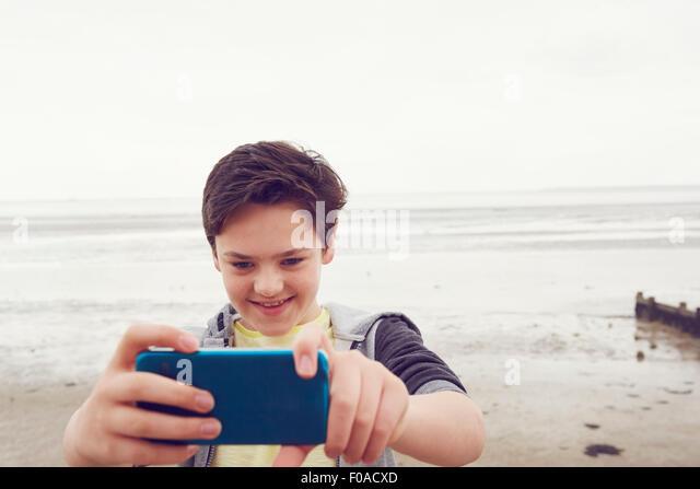 Lächelnde Teenager unter Smartphone Selfie am Meer, Southend on Sea, Essex, UK Stockbild