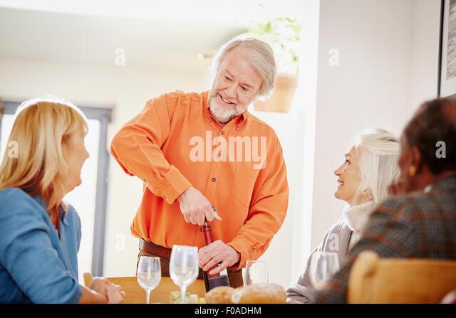 Senior woman Eröffnung Wein mit Freunden Stockbild