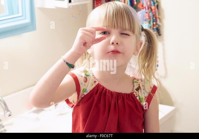 Porträt des jungen Mädchens, auf der Suche durch Finger Stockbild