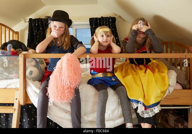 Drei Schwestern, sitzt auf Bett, tragen Fancy Dress Kostüme, abdecken, Mund, Ohren und Augen Stockbild