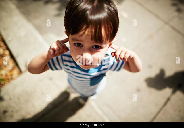 Porträt eines jungen, seine Finger in seinen Ohren auf Straße Stockbild