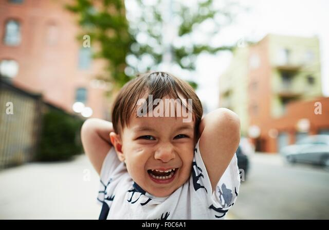Porträt von lachender Junge mit seinen Händen hinter dem Kopf Stockbild