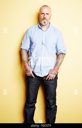 Reifer Mann mit Tattoos auf Arme und Hals, gelber Hintergrund Stockbild