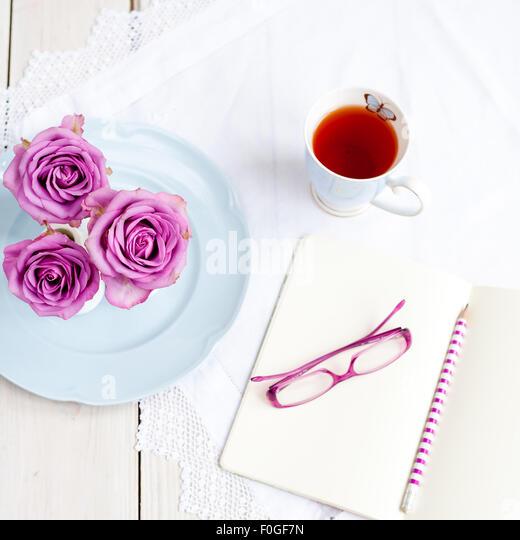 drei Rosa Rosen in Vasen auf blauen Teller mit Tasse Tee und Notizbuch mit Bleistift und Gläser öffnen Stockbild