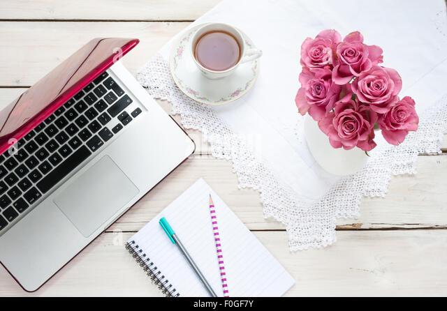 Arbeiten von zu Hause - rosa Rosen, Teetasse, Notebook, Laptop und Stifte auf dem Schreibtisch Stockbild