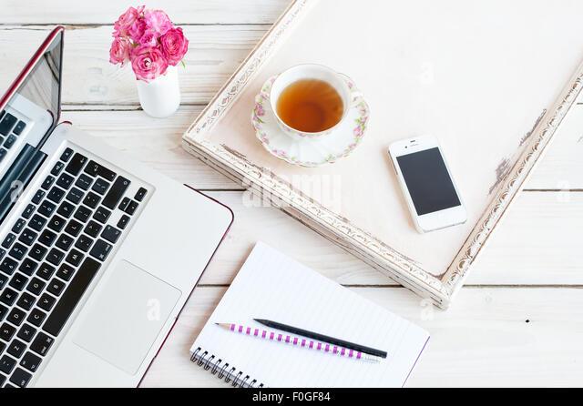 Arbeiten von zu Hause - Laptop, Notebook, Handy, Stifte, Tee und Rosen Stockbild