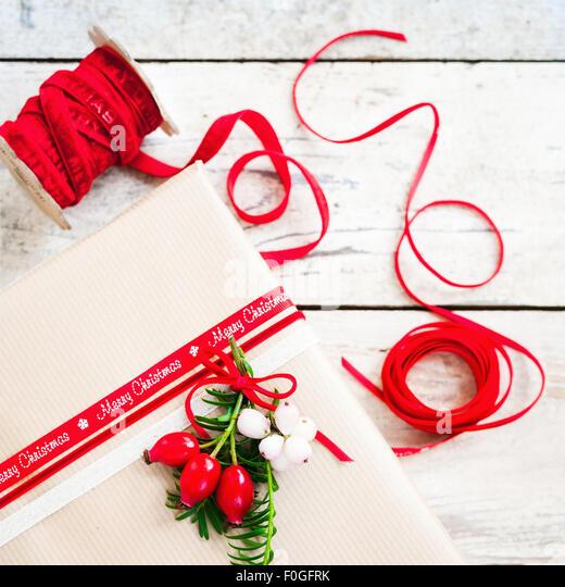 einfaches Geschenk mit braunem Papier eingewickelt und mit rotem Band und Beeren dekoriert Stockbild