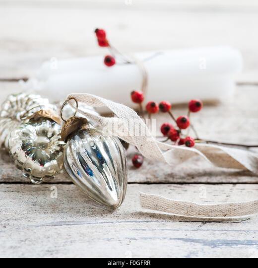 weiße Kerzen mit Bindfäden, roten Beeren und silbernen Kugeln gebunden Stockbild