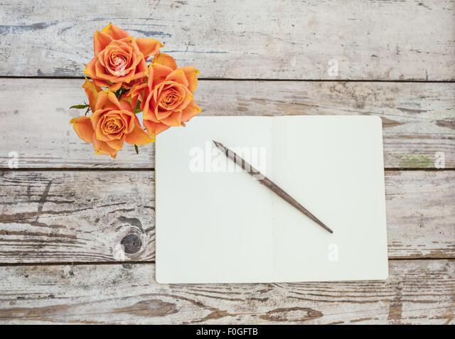drei orange Rosen auf rustikalen Holztisch mit offenen Notizbuch und Stift Stockbild