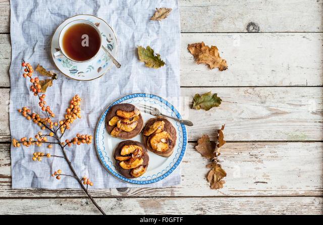 Pfannkuchen mit karamellisierten Äpfeln auf Vintage Teller mit Tee in Vintage Teetasse, Eichenlaub und Ilex Stockbild