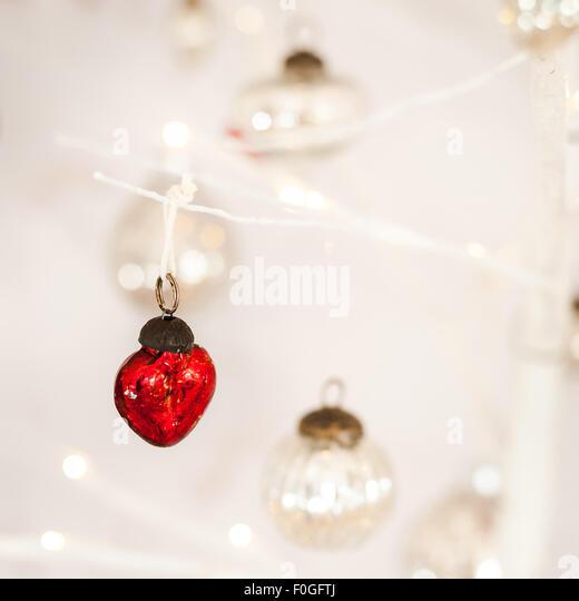 Nahaufnahme von einem herzförmigen roten Glas Christbaumkugel mit silbernen Kugeln und Bokeh im Hintergrund Stockbild