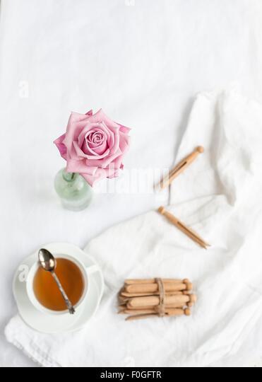 eine einzige rosa stieg im Fokus, mit unscharfen Hintergrund von weißem Stoff, Teetasse mit Teelöffel Stockbild