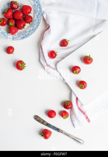 Erdbeeren in einem blau-weißen Teller und auf dem Tisch und hacken board Stockbild