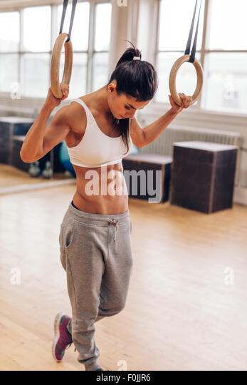 Passen Sie junge Frau, die das Training mit Gymnastik Ringe. Muskulöse Frau in Turnhalle blickte, Vorbereitung Stockbild