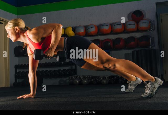 Junge Frau dabei einen Arm treiben im Fitnessstudio Stockbild