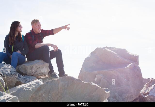 Junges Paar sitzt auf Felsen suchen Weg zeigen Stockbild