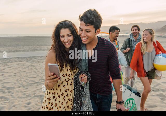 Gruppe von Freunden zu Fuß am Strand, junge Paar Smartphone betrachten Stockbild