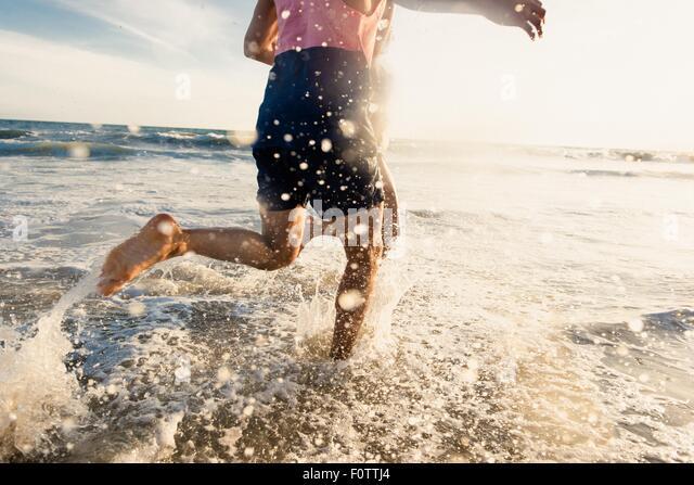 Junger Mann läuft im Meer, niedrige Abschnitt Stockbild