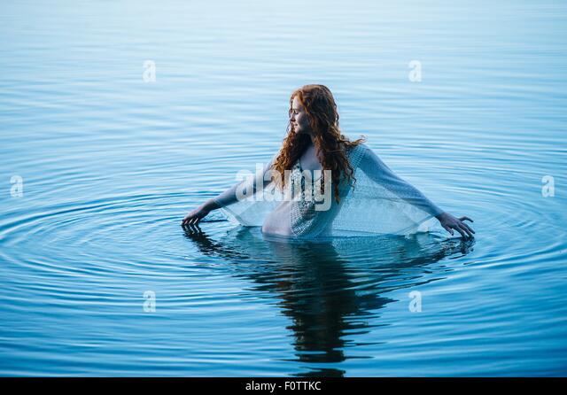 Junge Frau im blauen See Plätschern Oberfläche mit den Fingern Stockbild