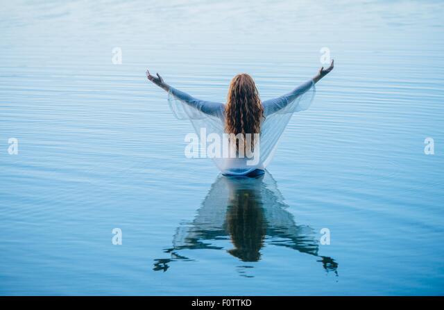 Rückansicht des jungen Frau im blauen See mit offenen Armen Stockbild