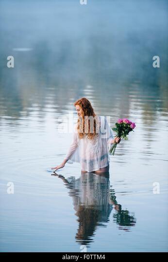 Junge Frau im See Holding Rosenstrauss und Plätschern Oberfläche mit den Fingern Stockbild