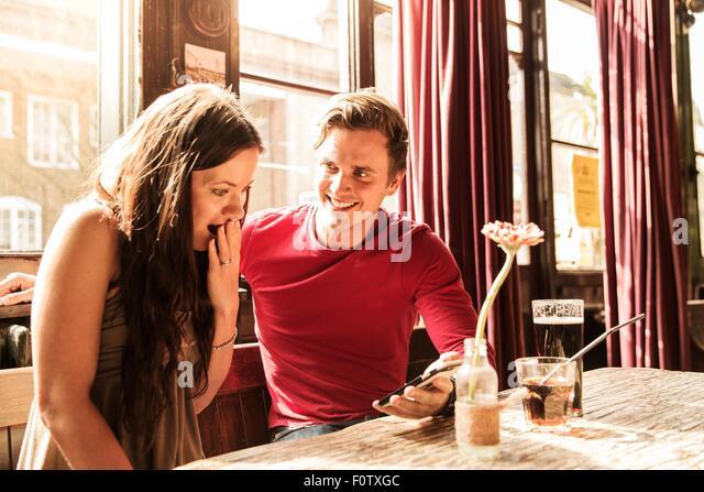 Paar mit Smartphone zusammen, Hand in den Mund Stockbild