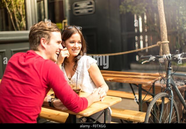 Paar-Sitzung von Angesicht zu Angesicht im Biergarten, die Hand in Hand Stockbild