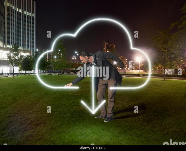 Künstler malen Wolke download Symbol außerhalb Bürogebäude in der Nacht Stockbild