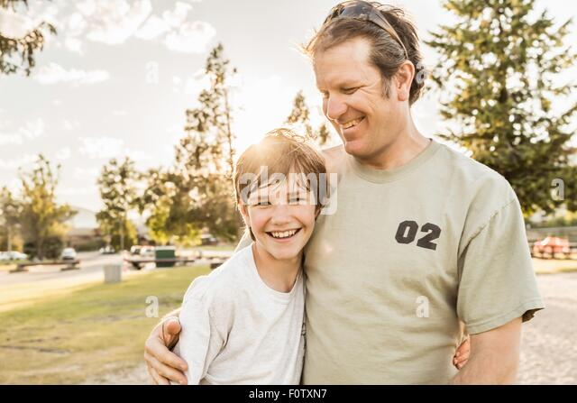 Vater und Sohn im Teenageralter lächelnd Stockbild
