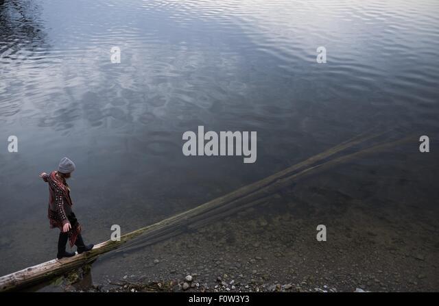 Frau balancieren auf gefallenen Baumstamm in See Stockbild