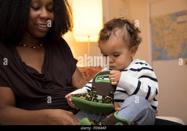 Mitte Erwachsene Frau und neugierig Kleinkind Tochter mit Baby boot Stockbild
