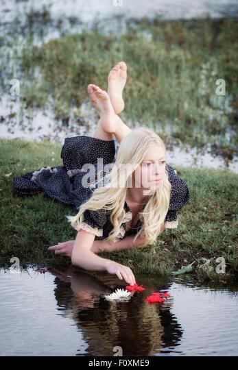 eine Blondine ist Blumen auf einem Teich platzieren. Stockbild