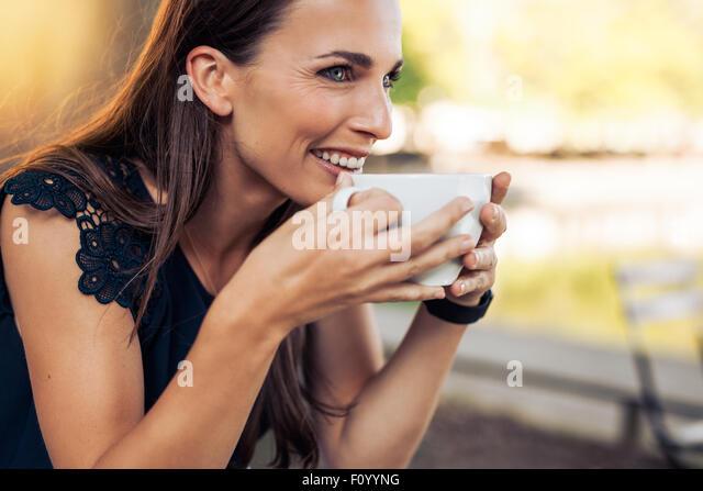 Junge Frau hält eine Tasse Kaffee und schauen weg Lächeln auf den Lippen. Kaukasischen Frauen trinken Stockbild