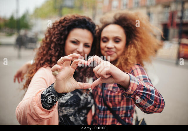 Glückliche junge Freundinnen machen Herzform mit Händen und Fingern. Zwei Frauen im Freien auf Stadtstraße Stockbild